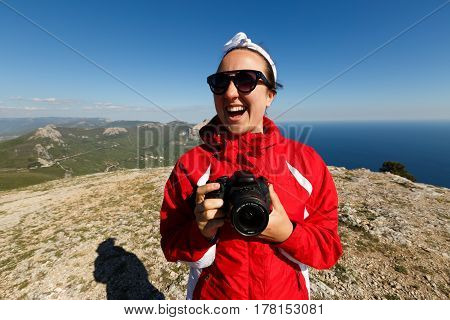 Happy woman photographer smiles on a peak of a mountain with dslr camera in her hands in mountains enjoying the climb with beautiful rocky and sea background outdoors.