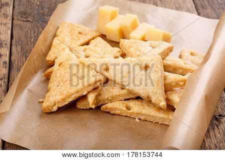 Homemade cheesy crackers shaped as slices of cheese. Perfect crispy snack.