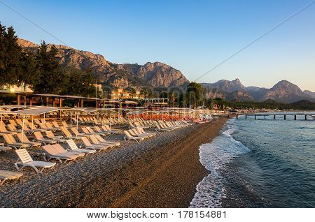 Hotel and plank beds with umbrellas on the beach against the backdrop of the mountains. Kemer.Turkey. Sunrise in the sea.