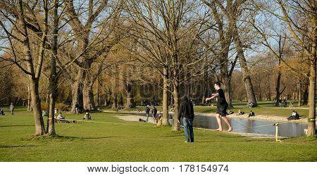 Munich,Germany-March 23,2017:A man walks on a slackline while other people relax during a warm spring afternoon in Munich's Englischer Garten