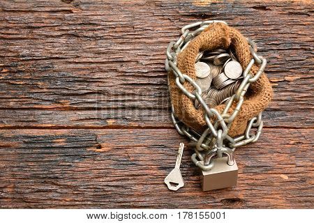 coins with chain with key and sack bag on with wooden background for business and financial concept.