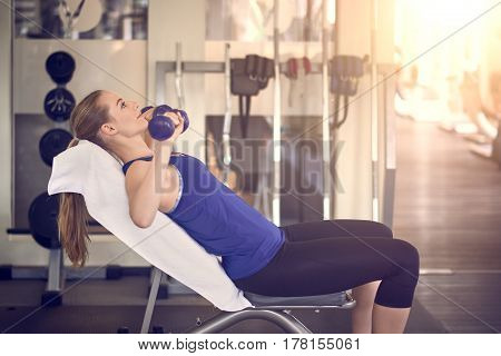 Attractive young woman working out in a gym training with a pair of dumbbells in a close up view in a health and fitness concept
