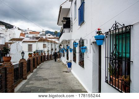 MIJAS SPAIN - FEBRUARY 08 2015: A street of Mijas pueblo (village) decorated with blue flower pots Malaga province Andalucia Spain.