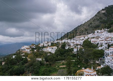 A panoramic view of a mountain and Mijas a small touristyc white-washed village at Malaga province (Andalusia Spain) on winter cloudy day.