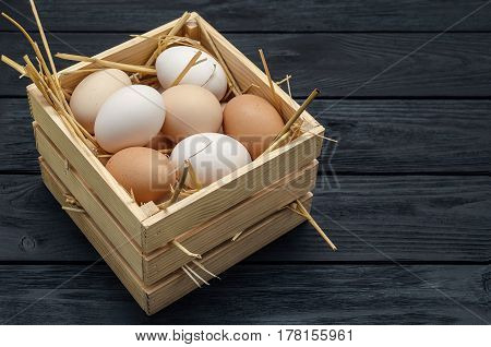 Easter eggs on a wooden desk. Black painted wood board background.
