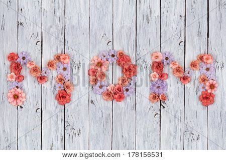 Mom Letters Made Of Handmade Paper Flowers Over An Aged White Wood Background