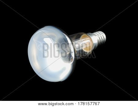 A light bulb is on black background