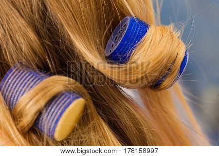 Woman curling her hair using rollers. Haircut concept