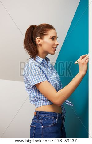 Pretty young woman sitting on the floor with paint brush: renovation concept