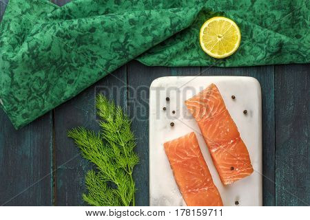 Two slices of salmon on a dark background with a place for text, with slices of lemon, peppercorns, and dill sprigs, shot from above with a place for text