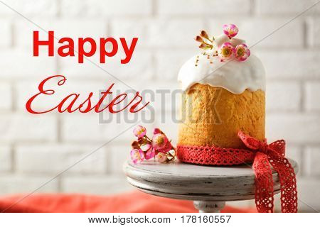Tasty traditional cake on wooden stand. Text HAPPY EASTER on background