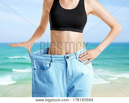 Young woman in huge pants on seascape background