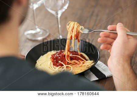Young man eating pasta at table, closeup