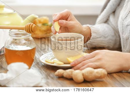 Woman with herbal cup of tea sitting at kitchen table