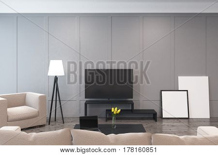 Living room interior with a tv set armchairs and two framed pictures standing on the floor near a gray wall. 3d rendering. Mock up
