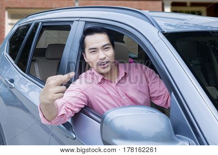 Portrait of a male driver looks angry and expressing his road rage by showing a middle finger