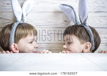 Two Cute Little Brothers Wearing Bunny Ears Playing Egg Hunt On Easter. Adorable Children Celebrate