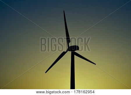 Wind turbine backlit with intense color background at dawn
