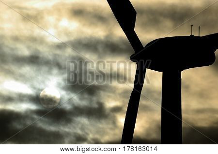Wind turbine backlit in foreground with sun behind the clouds