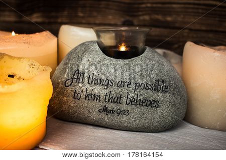 a stone with christian scripture with light candle