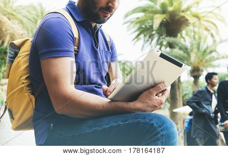 Hipster person holding in hands digital tablet with blank screen man reading on computer on background nature park palm landscape mock up technology blur male hands tourist using gadget smile