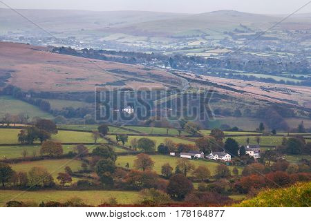 The village and farmlands in the Dartmoor National Park. Evening and haze. Autumn. View from Brentor. Devon. England
