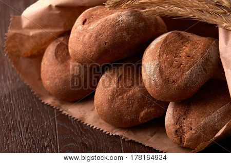 loafs of brown bread, packaged in a paper bag on wooden background. Brown table. Decorative rope. Tasty and appetizing. Delicious food.