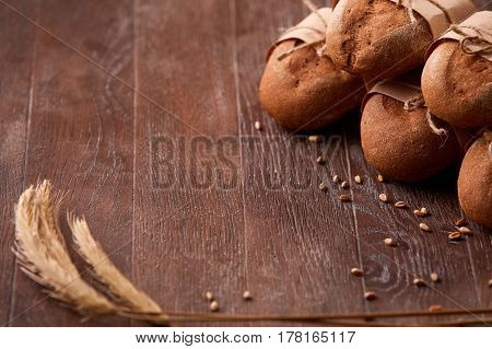 different bread on the wooden table, wheat, paper bags, rope, ears of wheat. Brown background. Delicious food. Fresh baking. Tasty and appetizing. Angle position.