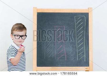 Cute boy with glasses drawing graph chalk