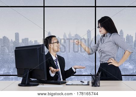 Young businesswoman pointing to her subordinate as angry expression with winter background on the window