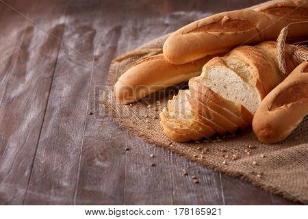Slices of white bread with baguette on burlap on the dark wooden table, Space for text. With wheat and ears of wheat. Delicious food. Fresh baking. Tasty and appetizing. With flour.