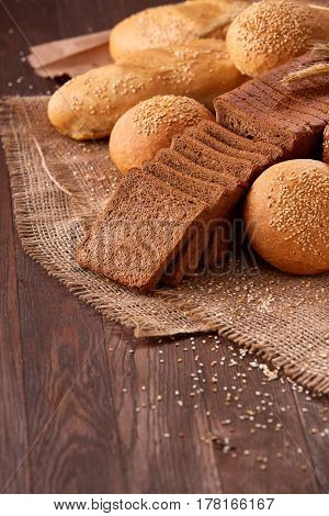 Assortement of bread on burlap on the wooden table. Slices of bread and roll. With wheat and ears of wheat. Delicious food. Fresh baking. Tasty and appetizing. Vertical photo.