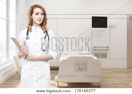 Red haired woman doctor is holding her clipboard while standing in a ward with a bed an armchair and a tv set. 3d rendering mock up