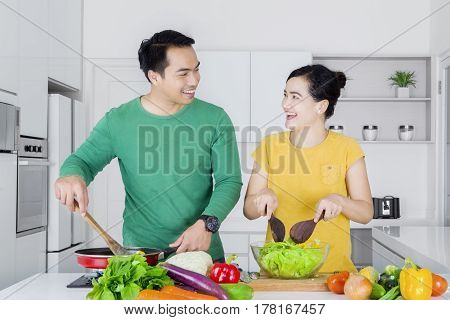 Photo of two cheerful Asian couple cooking in the kitchen while looking to each other and laughing together