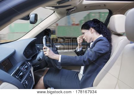 Picture of Indian businesswoman looks dizzy driving a car while massaging her forehead