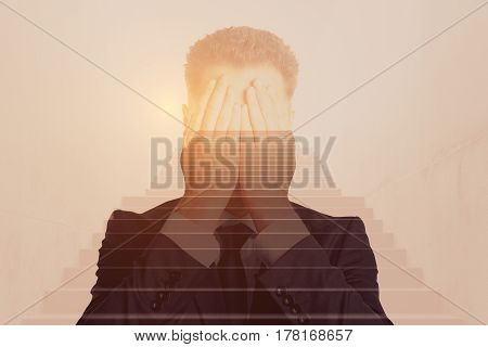 Stressed young businessman covering face with hands on abstract light background with staircase. Growth and risk concept. Double exposure
