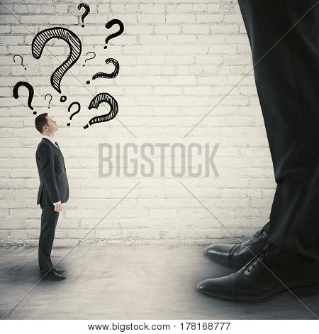 Side view of tiny businessman with drawn question marks looking up to huge one. Small and big businesses concept
