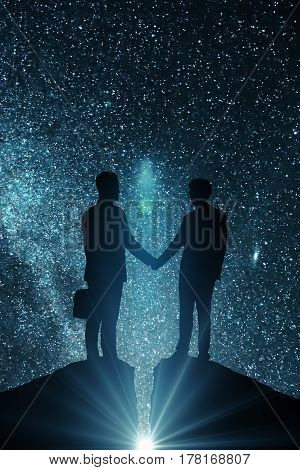 Side view of businessmen silhouettes shaking hands on open space background. Teamwork concept