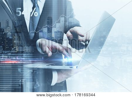 Businessmen using laptop together on city background. Technology and teamwork concept. Double exposure