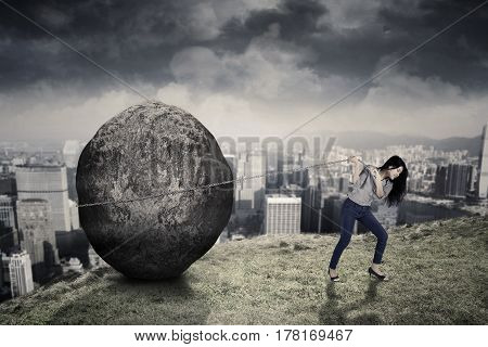 Young female entrepreneur is pulling big stone with a chain while walking on the hill