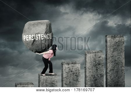 Photo of a female worker climbing a chart while carrying a big stone with a persistence word on her back