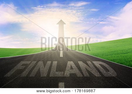 Picture of empty road with word of Finland and arrow upward at the end of a road