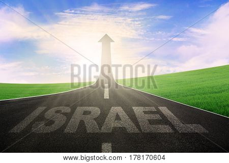 Image of empty way with word of Israel and arrow upward at the end of a road