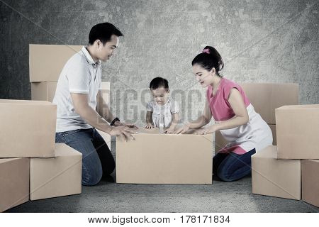 Picture of young parents and child are packing cardboard together and moving to a new house