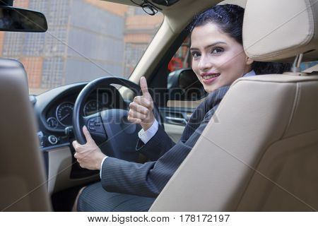 Successful Indian businesswoman driving a car and showing thumb up with container background on the car window