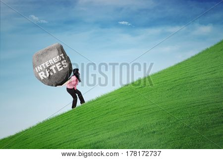 Businesswoman climbing a hill while carrying a boulder with text of interest rates. Concept of big interest rates