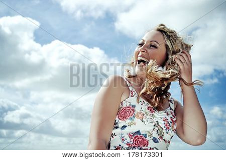 Smiling young blonde woman with curly hair wearing a flower print summer dress is laughing in the gust of wind. Sky background.