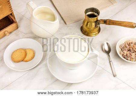 A cup of cappuccino with butter cookies and a milk jar on a white marble table, with a place for text. Selective focus