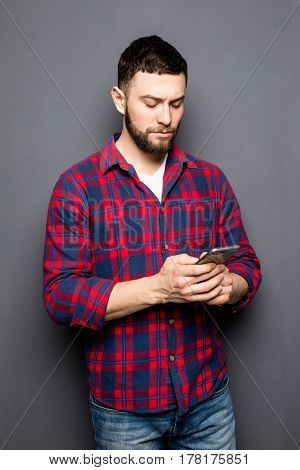 Confident Young Man Holding Smart Phone And Looking At It While Standing Against Grey Background