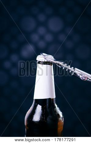 Glass bottle of beer and opener on a dark background. Hand opening a bottle. Alcohol and drinks concept.